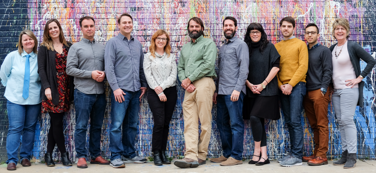 Group photo of the members of the Office of Sustainability team. There are 11 people in the picture in front of a bright, multi-colored background.
