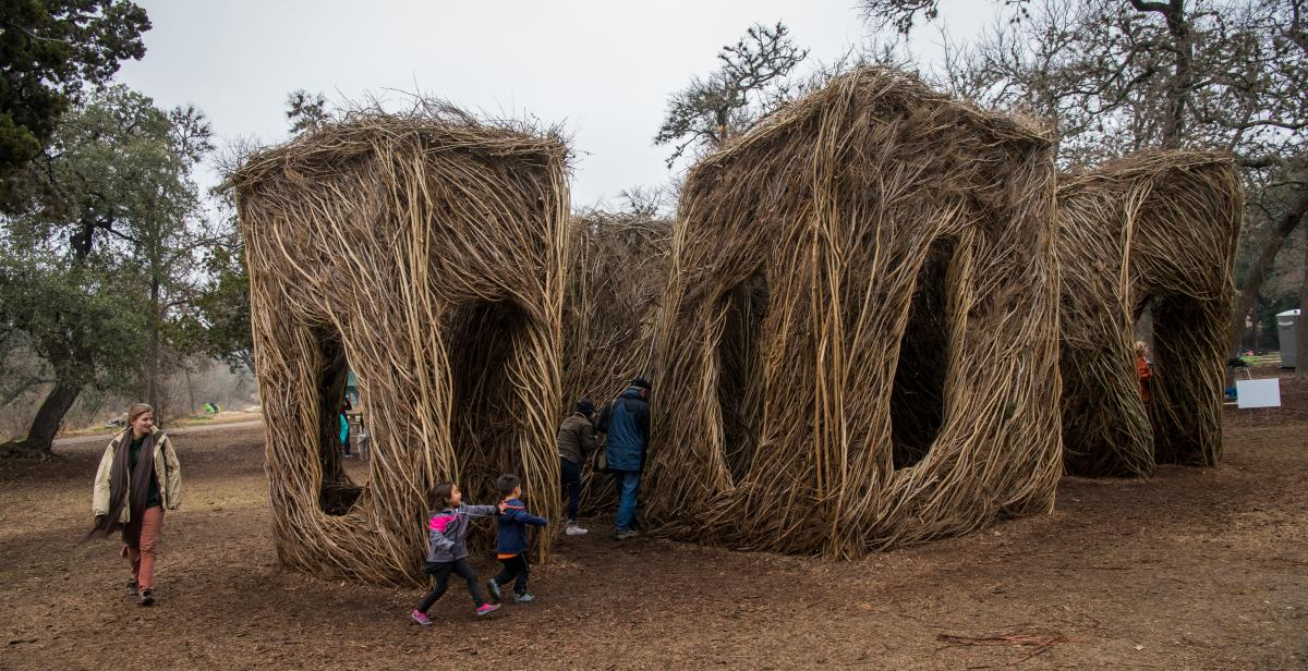 Artwork made of large sticks that children are runnign around and playing inside of.