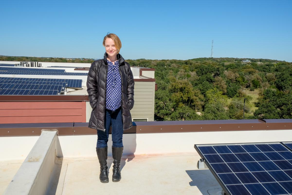 Susan Peterson standing on a rooftop. There are solar panels around her and a view of the hill country to her right.