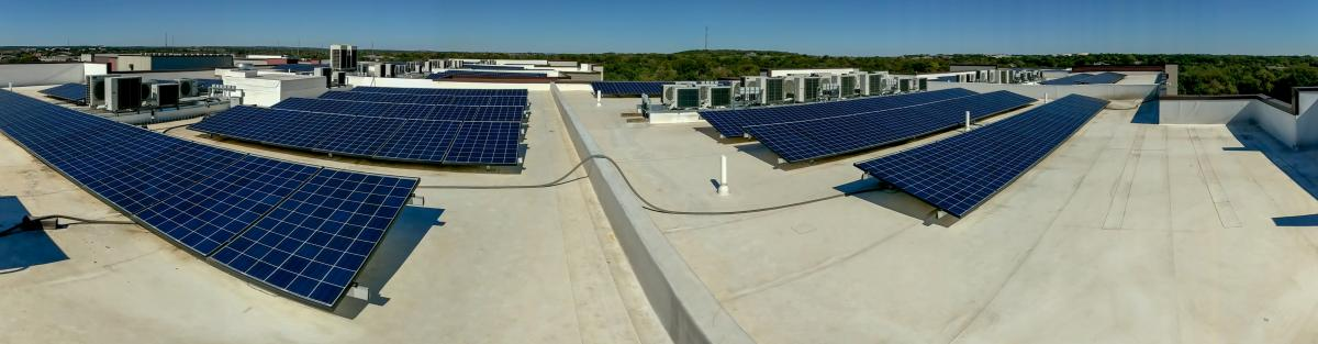 Panoramic view of a large rooftop solar array under a blue sky. Trees and hills are on the horizon line.