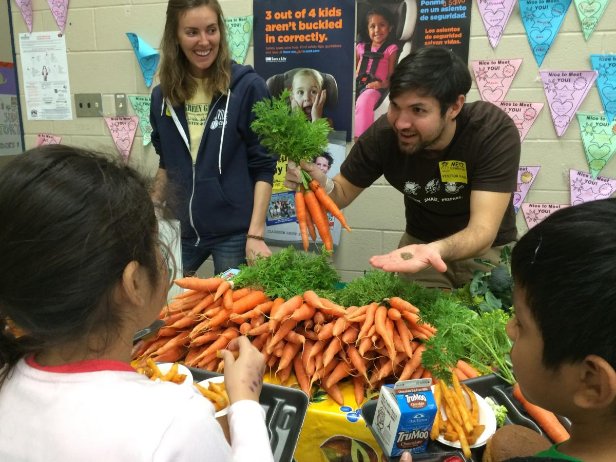 Man showing carrots to a school age kid.