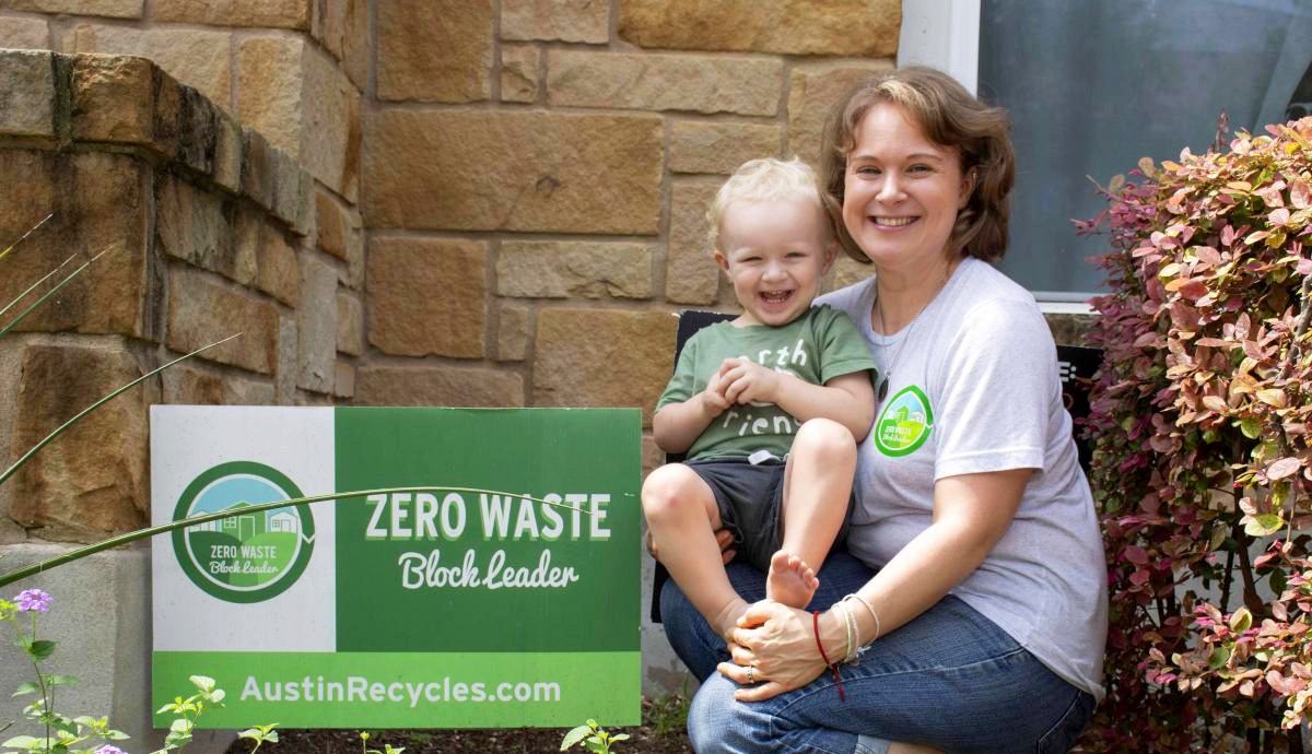 "Taylor with her son outside of her home next to a sign that reads ""Zero Waste Block Leader austinrecycles.com"""