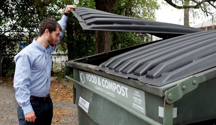 Tom Gleason looking in a large composting bin.