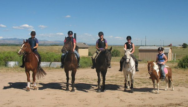 Six people on horses, ont he far right, a child is riding a pony. There is blue sky and mountains in the background.
