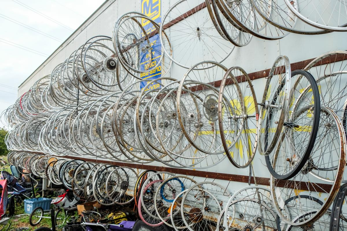 Bicycle wheels all hung up on the side of a trailer outside on a grey day.