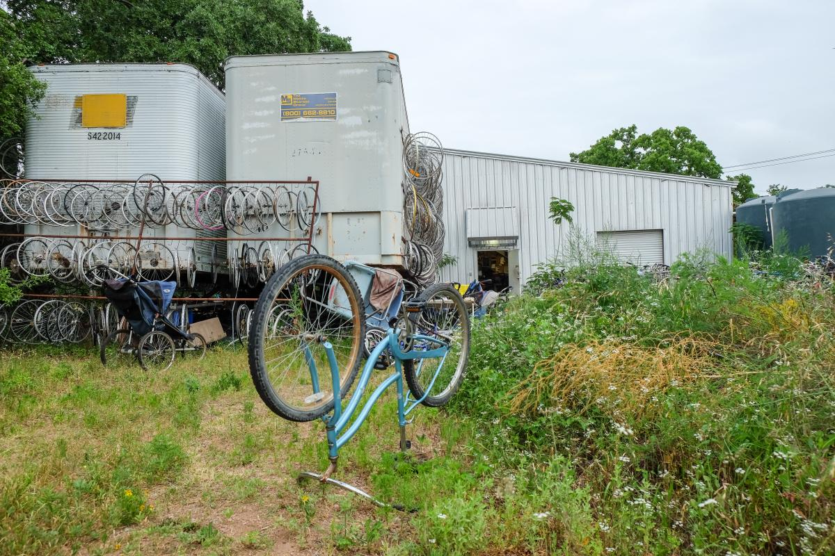 Three sheds with bicycles and wheels in front of it. In the foreground, a bicycle stands upside down.