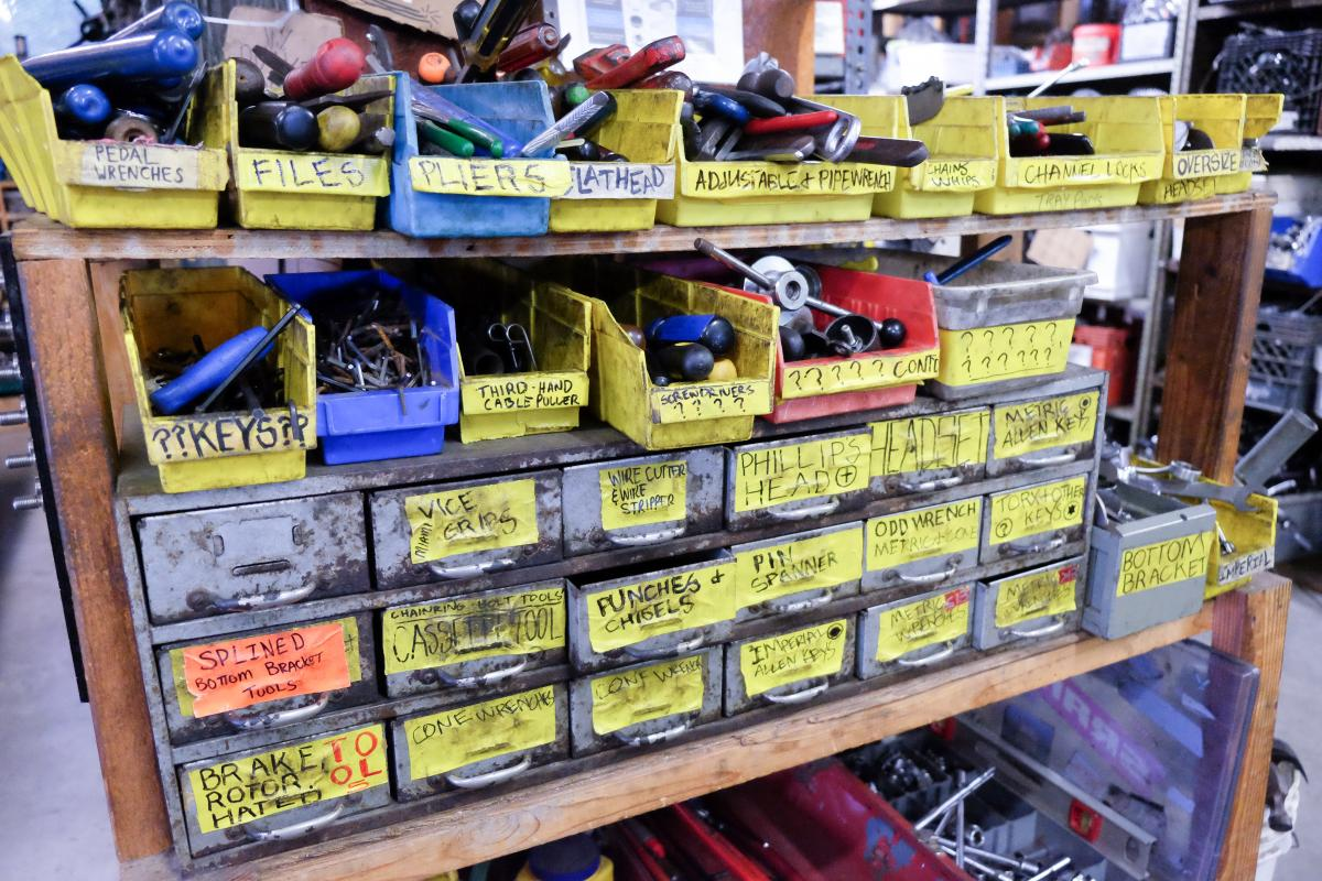 Bicycle parts in bins with yellow labels.