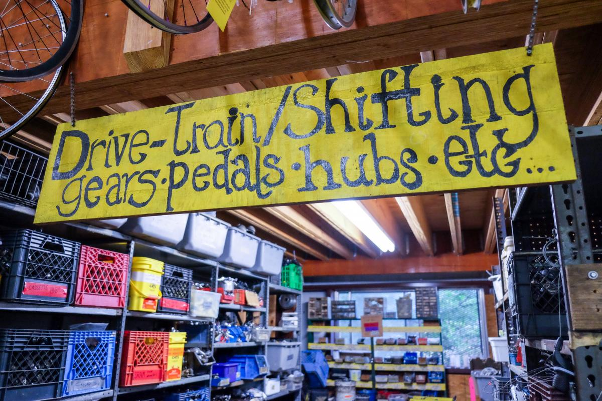 "Interior of bicycle shop. Sign reads ""Drive-train/Shifting gears, pedals, hubs, etc..."""