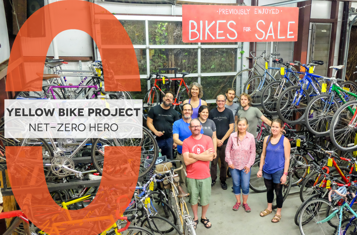 "Net-Zero Hero logo with text, ""Yellow Bike Project Net-Zero Hero"" overlayed on group picture of Yellow Bike Project volunteers in the shop surrounded by bikes. Sign above them says ""Previously enjoyed bikes for sale""."