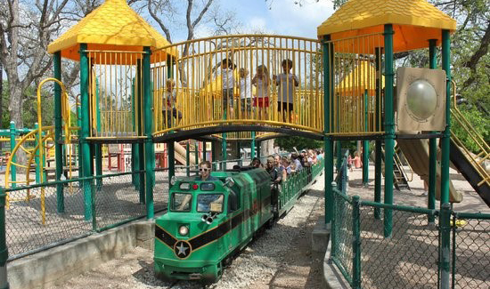 Playscape with bright yellow shade cones and bars with kids playing on the upper deck. A green train is going through the playscape.