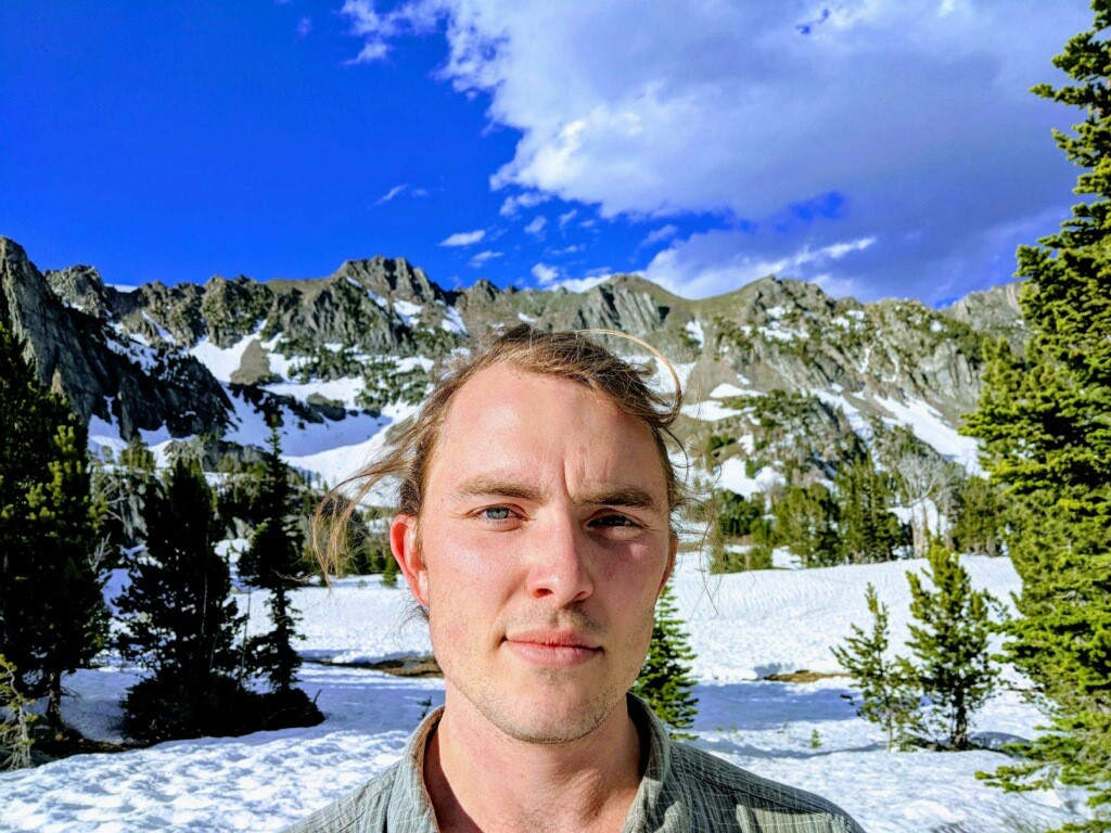 A selfie of Brooks Bailey standing in front of snowy mountains in Big Sky, Montana.
