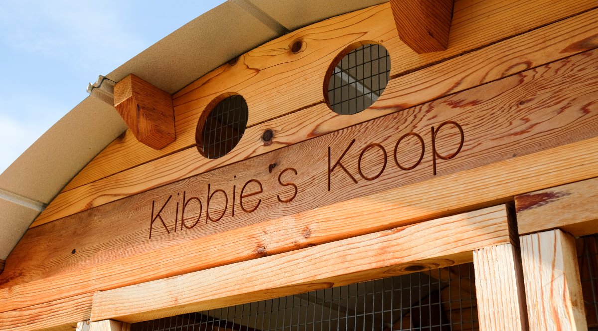 "Detail shot of chicken coop that reads ""Kibbie's Koop"""