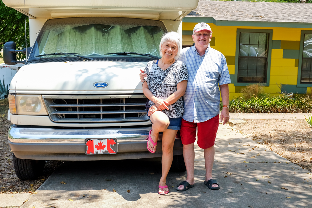 A couple standing in front of an RV smiling. The RV is parked in the driveway of a yellow one-story hourse. The license plate is canadian.