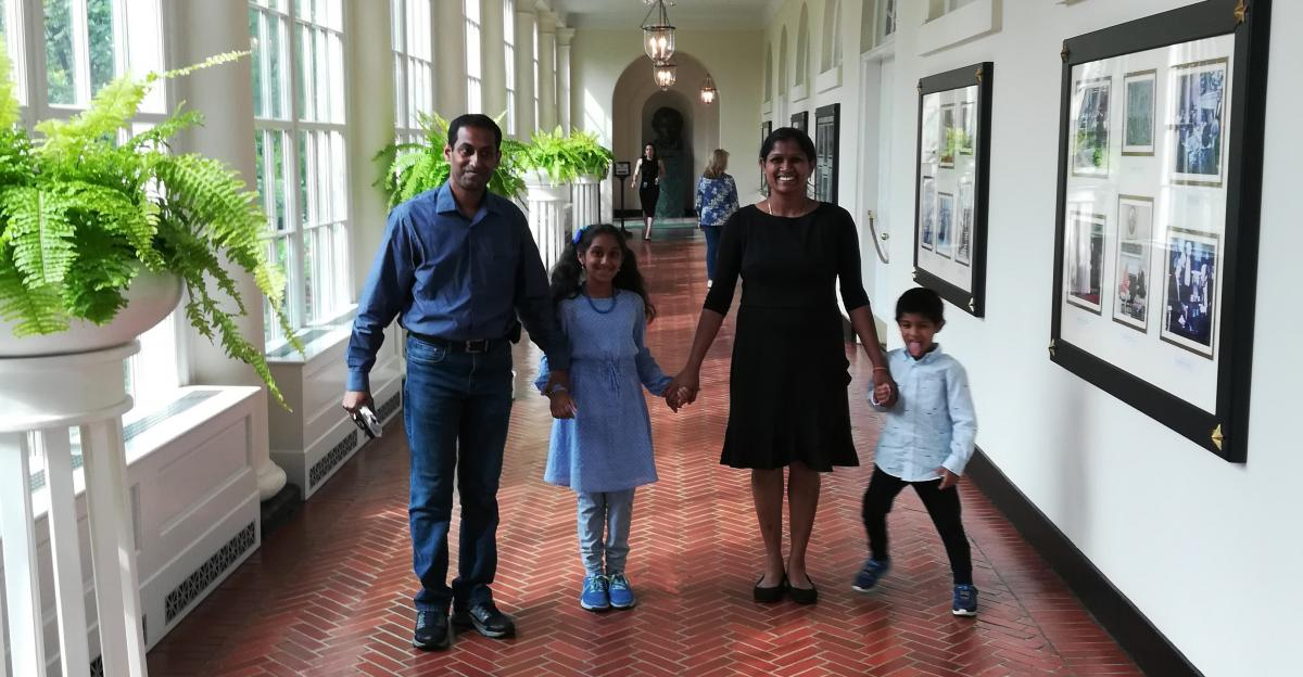 Asvini with her mother, father, and brother holding hands in the white house.
