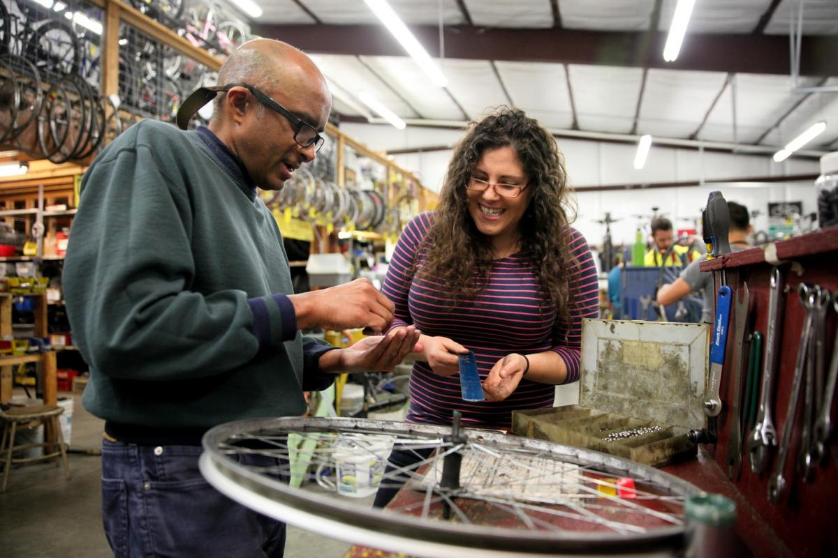 Person showing another person how to fix a bicycle wheel in a bicycle shop.