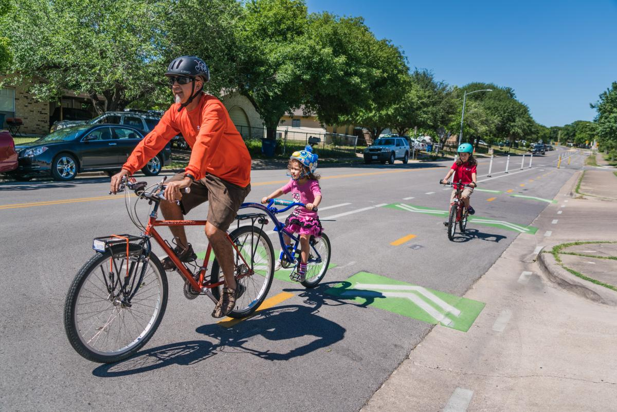Adult and two children riding bicycles in designated bicycle lanes.