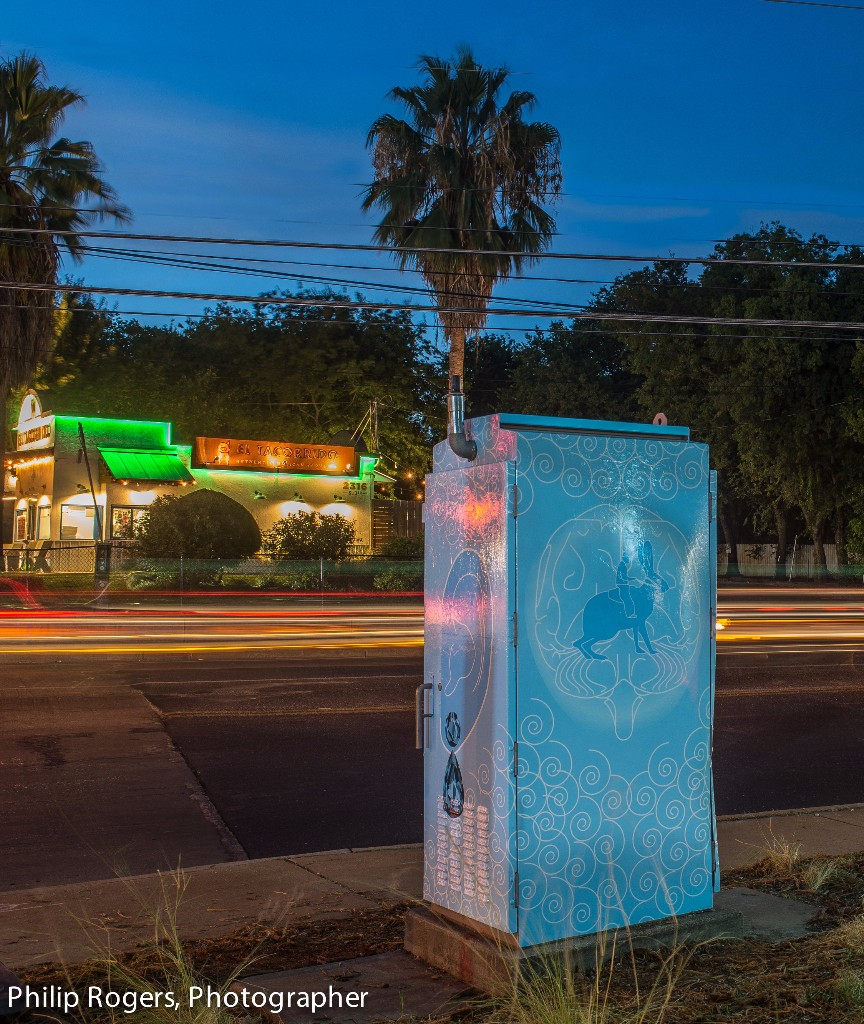 View of a colorful art box near a sidewalk at night.