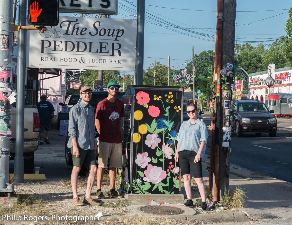 Volunteers standing in front of a designed artbox painted with flowers.