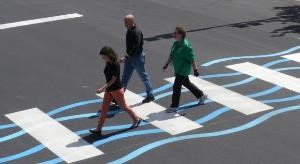 Photo of people crossing a crosswalk painted to resemble water