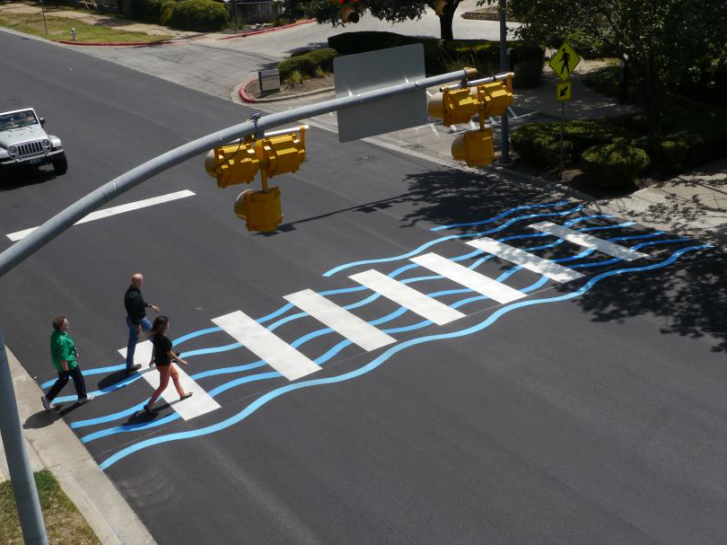 A creative crosswalk with a blue ripple paint design on Lake Austin Boulevard.