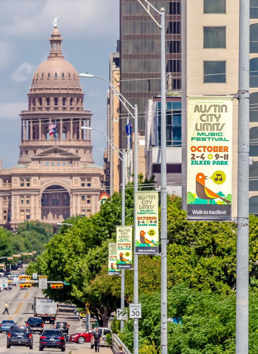 View of a line of street banners for Austin City Limits in front of the Capitol building.