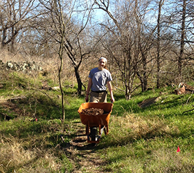 From Trashed to Treasured Property: The Grove Landfill Story.  An AmeriCorps olunteer hauls mulch for new trails.