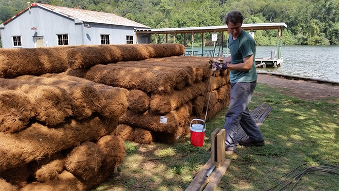 Coir logs, woven logs made of coconut husk fiber, are staged and prepped at Commons Ford Park for shoreline installation.