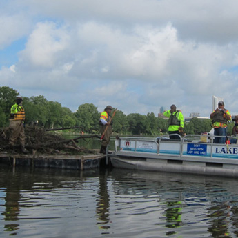 Several employees working from a boat. The Watershed Protection Department collects 250 tons of trash from the Lady Bird Lake each year.
