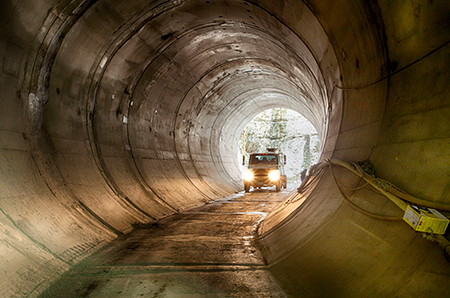Photo of truck driving through tunnel during construction.