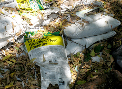 Improper disposal of herbicide (weed killer) on the ground adjacent to an alleyway.