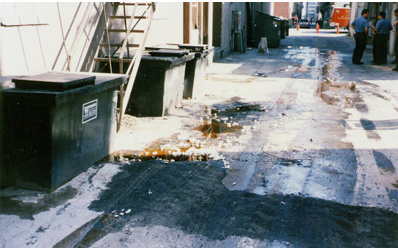 Grease spill in alleyway during servicing of restaurant grease bins.