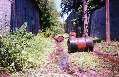 Leaking solvent drums illegally dumped in alleyway.