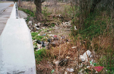 Bags of trash dumped in a creek from a residence.