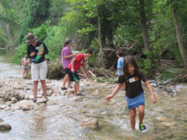 A school class walking through a creek.