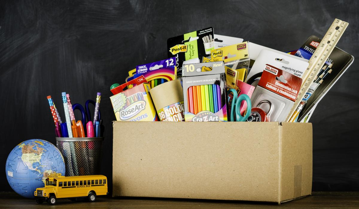 Back-to-school items like markers, crayons, pencils, scissors and a ruler in a box