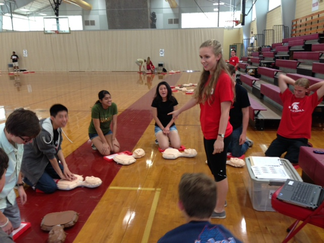 A student leading a TAKE10 Compression Only CPR class in the gym at St. Stephen's Episcopal School in Austin