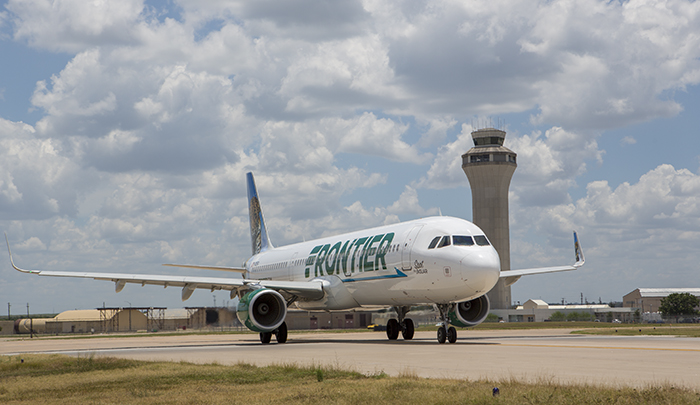 Frontier plane in front of Austin Airport control tower