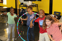 Children with hula hoops inside the Rosewood Recreation Center