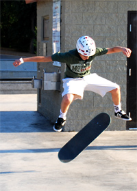 Youth jumping in the air while flipping skateboard