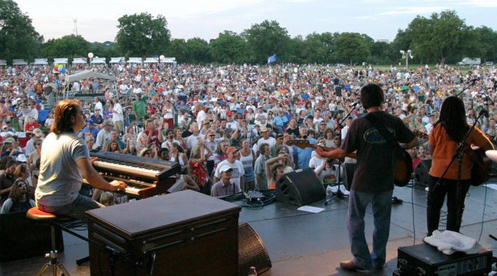 """musicians on stage playing music to a large audience in a park"""