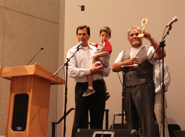 Former city councilman Raul Alvarez and President of ALMA with son honoring Gilbert Alba with special award .