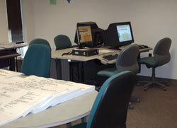 photo of plan room with pc's and planning documents on a table