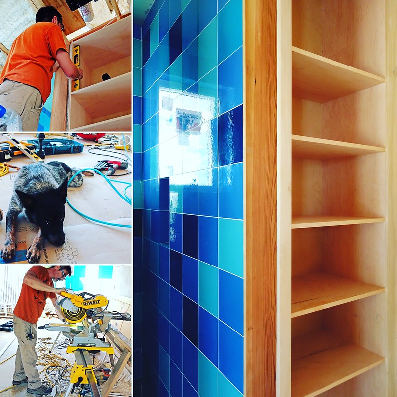 Person working on placing blue tile.